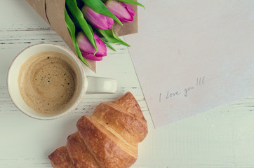 Cup of coffee with croissant, bouquet of pink tulips and notes I LOVE YOU