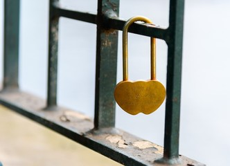 Bridge love lock, with shallow depth of field and hanging from a green metal fence on the Yarra River in Melbourne Australia
