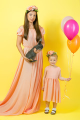 beautiful young mother and daughter in beige dresses with wreathes on their hads with bunny in photo studio on yellow background