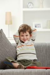 Portrait of smiling kid sitting on sofa at home