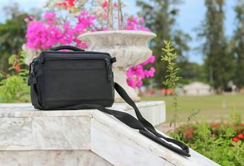 black  bag on banister marble floor in the park