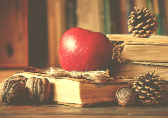 Old vintage books on wooden table with red apple, pine cones, walnuts on bookshelf background.