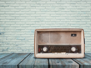 Old retro radio on wood table with brick wall background