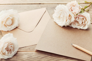 Envelope or letter, paper card and vintage rose flowers on rustic wooden table for greeting on Mother or Woman Day.