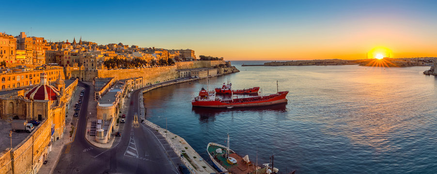 Valletta, Malta - Panoramic skyline view of Valletta and the Grand Harbor with beautiful sunrise, ships and clear blue sky