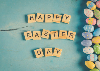Colorful easter egg and wood text Happy Easter Day on blue wood