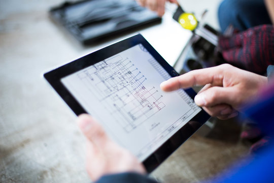 technician holds tablet with mechanical drawing
