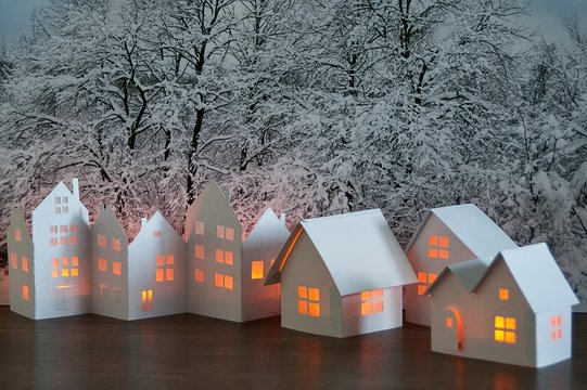 Close up of handmade small white cardboard houses with illuminated windows on snowy trees background. Winter decoration.