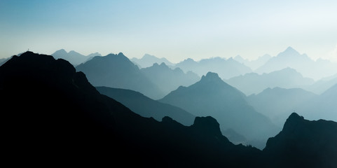 Spectacular blue and cyan mountain ranges silhouettes. Summit crosses visible. Wall mural