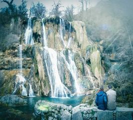 Amoureux assis devant une cascade