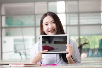 Portrait of thai high school student uniform beautiful girl using her tablet.