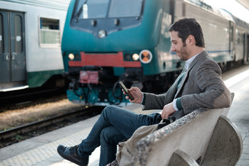 man waiting for the train seated in a train station platform