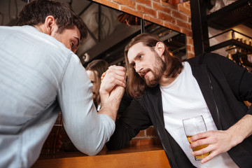 Drunk friends playing in arm wrestling