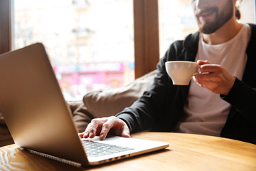 Cropped image of Bearded man using laptop in cafe