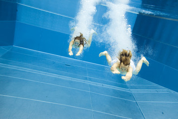 Underwater View Of A Young Couple Jumping Into The Water