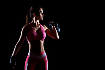 Dark contrast photo of young beautiful fitness woman which training in gym. Working out with dumbbells on black background