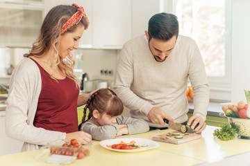 Happy young family preparing lunch