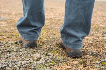 Foto a nivel del suelo de botas de montaña de hombre sobre suelo lleno de musgo