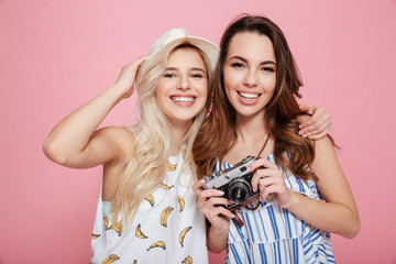 Two smiling pretty young women with old vintage photo camera