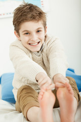 Happy smiling young boy stretching for his toes