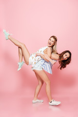 Cheerful woman holding her friend on back and having fun