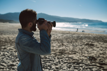 Young man taking a photo on the beach
