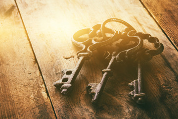 close up of vintage skeleton keys over wooden table
