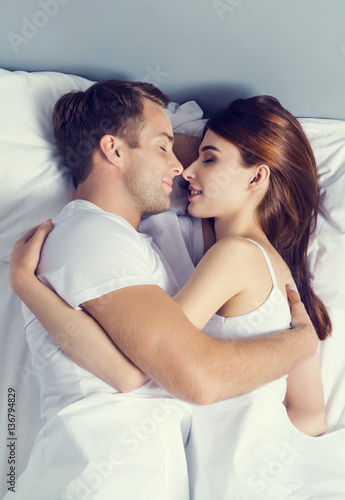 Young Sleeping And Hugging On The Bed In Bedroom
