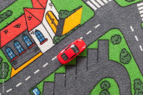 red toy car on a city themed carpet city street concept stock