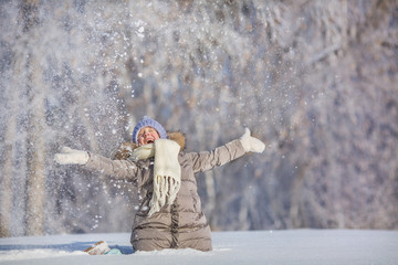 Little girl throws up snow and laughs in winter