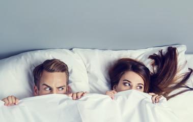 Obraz Playfull couple peeping from bedsheet - fototapety do salonu