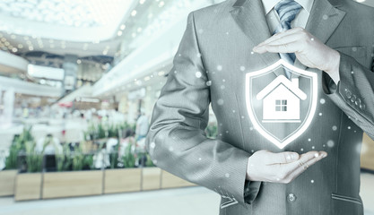 House protection and insurance. Home shield. Real estate safety. Blurred mall background.