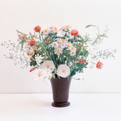 Bouquet of wild flowers on a white background. Space for text.