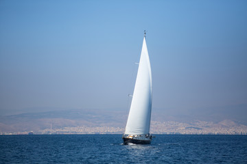 Sailing yacht with white sails in the sea near coast.