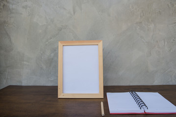 photo Frame on a wooden table and book on Gray wall background .