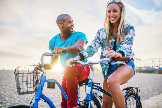 happy couple riding bikes together during sunset at santa monica california