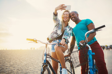 couple taking a break from riding bikes to take selfies