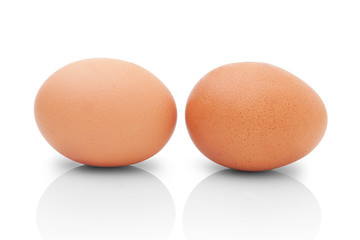 Two brown chicken eggs for cooking. Profile shot. Isolated on white background with shadow reflection. Two brown chicken eggs for baking, on white background. Two eggs to kitchen. Two eggs