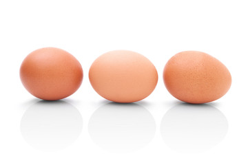 Three brown chicken eggs for cooking. Profile shot. Isolated on white background with shadow reflection. Three brown chicken eggs for baking, on white background. Three eggs to kitchen. Three eggs