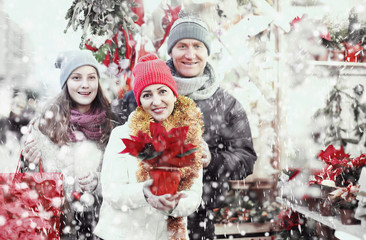 family of three with teenage girl choosing  floral decorations