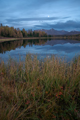 Mirror Surface Lake Autumn Vertically Orientated Landscape With Mountain Range On Background