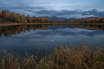 Mirror Surface Lake Autumn Landscape With Mountain Range And Moon On Background