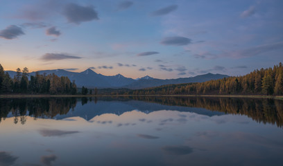 Mirror Surface Lake Pink Sunset Light Autumn Landscape With Mountain Range On Background