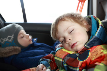 Two brothers sleeping in car