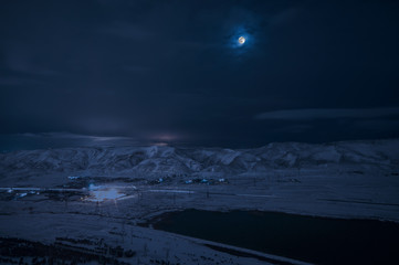 Landscape of snowy mountains and lake with full moon above. The moon and clouds on sky. Baku, Azerbaijan, Xojasan Lake