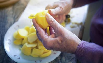 closeup of older woman hands cutting potatoes.