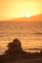 Couple in love taking pictures on the beach at sunset.