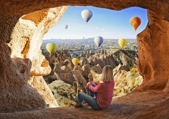 Woman watching  like colorful hot air balloons flying over the valley at Cappadocia, Turkey. Volcanic mountains in Goreme national park