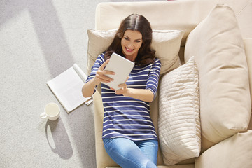 Chilling at  home Young brunette woman using her digital tablet while relaxing at home.