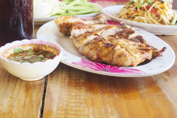 Thai style spicy meal, chicken grilled with spicy papaya salad and cold drink